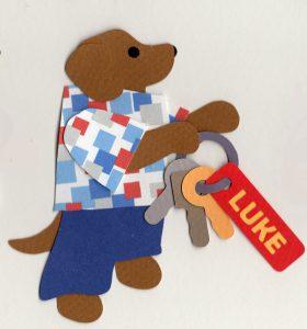 "K for Keys, Dog holding keys with tag labeled ""LIUKE"""