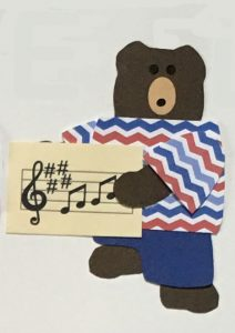 M for music, Bear holding a sheet of music