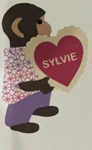 "V for valentine, Monkey holding a red valentine heart with a lace border and the name ""SYLVIE"" on it"
