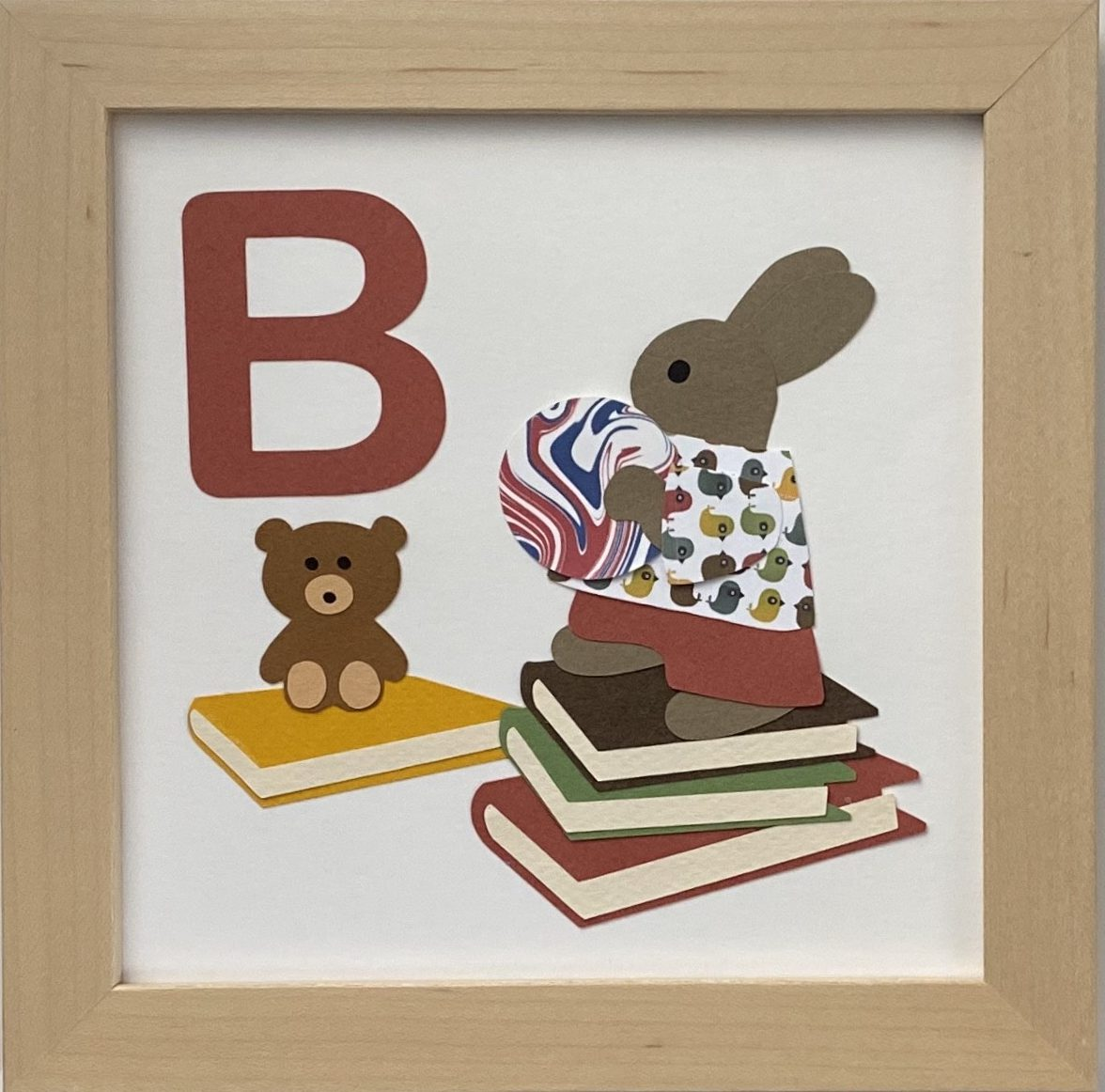 B initial sign - a rabbit with books, a toy bear, and a ball